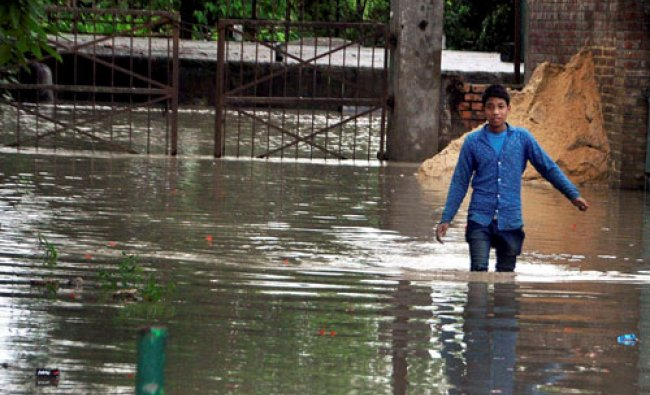 A man walks on a road flooded with rain water at Khurai Lai Wangma, Imphal East on Sunday...