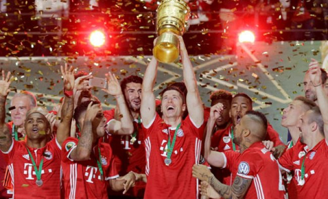 Bayern\'s Robert Lewandowski holds up the trophy after the German soccer cup...