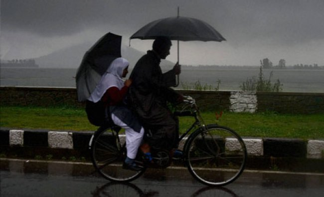 A cyclist with his daughter pedals his cycle holding an umbrella...