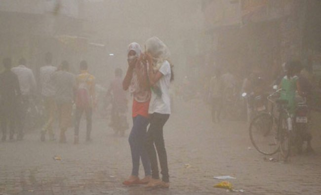 Girls cover themselves during a dust storm in mathura on Monday...