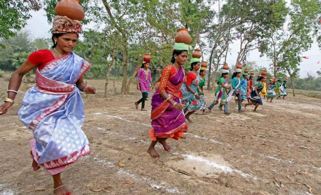 Women of a tribal community take part in pitcher race during a tribal festival in Birbhum district..
