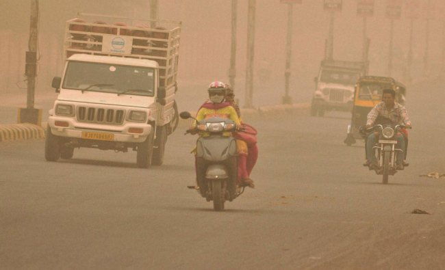 Vehicles moving on a road during a dust storm in Bikaner...