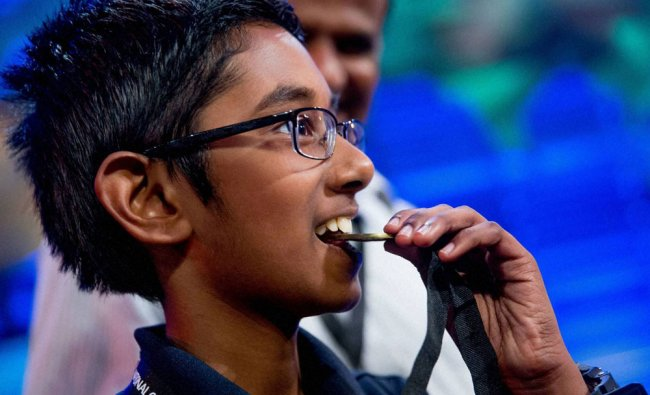 Rishi Nair of Florida bites his metal after winning the 2016 National Geographic Bee...