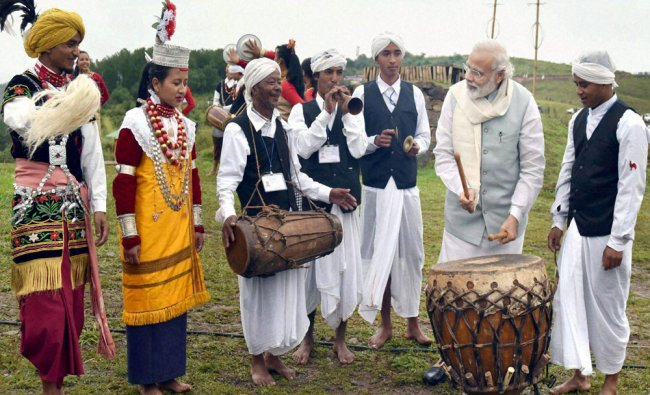 Prime Minister Narendra Modi with artists tries his hands at a drum in Heritage Mawphlang...