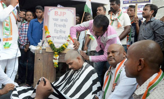 Congress workers shave their heads at a protest on NDA Governments\' second anniversary...