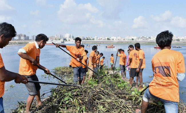 Volunteers clean Tapi river to celebrate the completion of two years of Modi government...