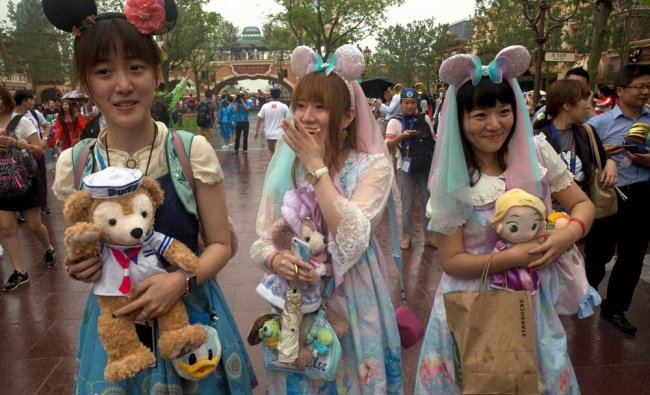 Visitors dress up as they attend the opening day of the Disney Resort in Shanghai...
