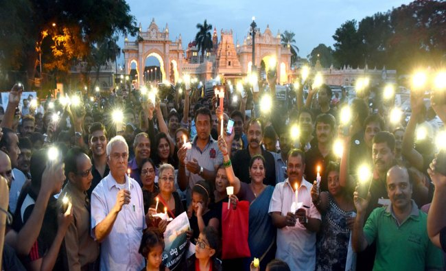 Members of various organisations take out a candle light march against construction activities...