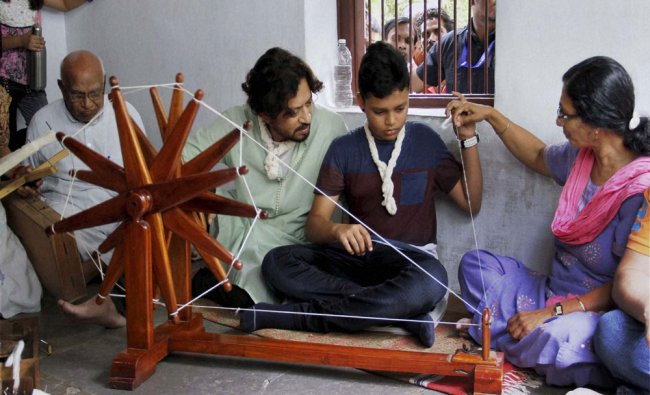Actor Irfan Khan along with his son spinning cotton on a Charkha during a visit to Gandhi Ashram..