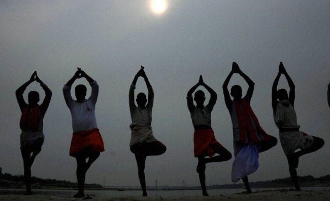 Local priests performing Yoga on the eve of International Yoga day in Allahabad on Monday...