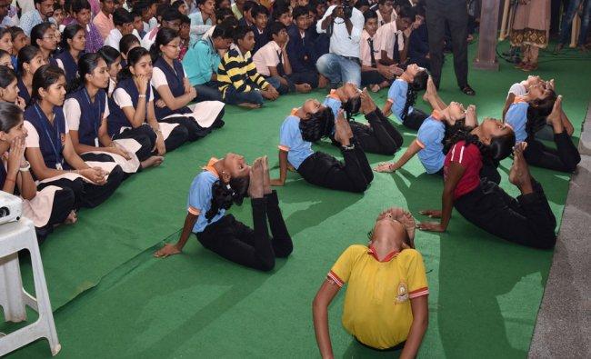 Students perform Yoga as part of International Yoga Day celebrations at Sarvagnya & Justice Shivraj
