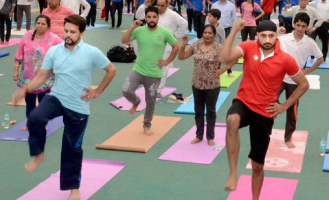 BCCI president and MP, Anurag Thakur with Indian cricketer Harbhajan Singh, performing yoga....