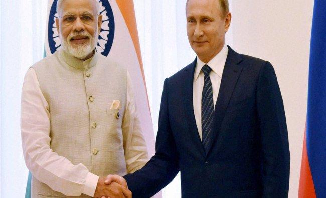 Prime Minister Narendra Modi shakes hands with Russian President Vladimir Putin during...