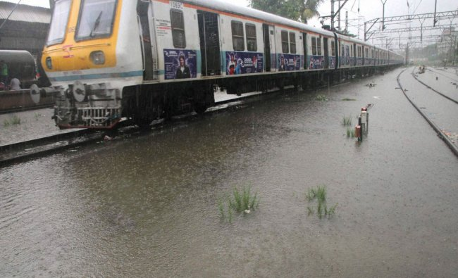 Local train on water logged railway track in Thane on Saturday. Local train services...