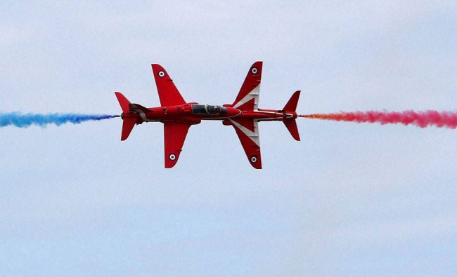 Two planes perform a dramatic fly past, during a display of the Red Arrows Display Team...