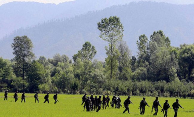 Army persons move towards the house where a Hizbul Mujahideen militant was hiding...