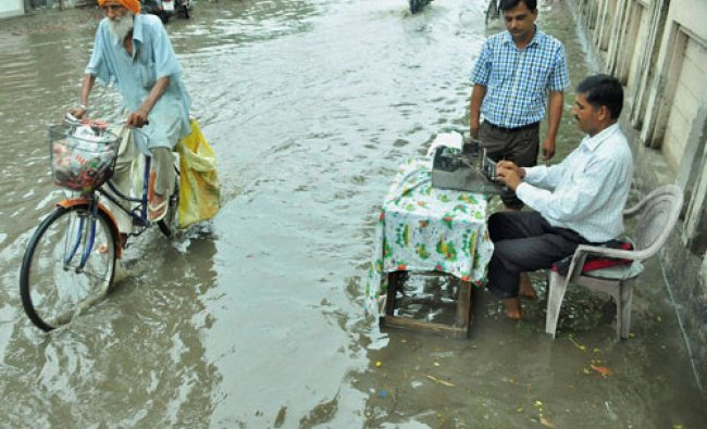 A typist attends a customer at a street flooded after heavy rains outside Court complex...