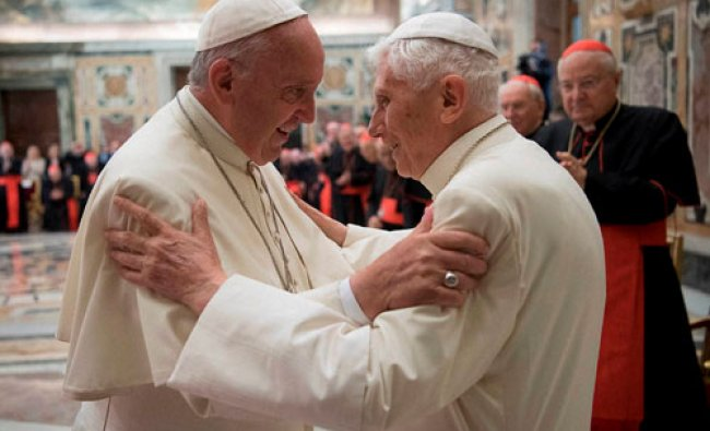 Pope Francis, left, and retired Pope Benedict XVI embrace during a ceremony...