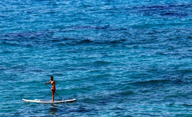 A man paddles on a stand-up board in the Mediterranean sea near Marseille as summer temperatures...