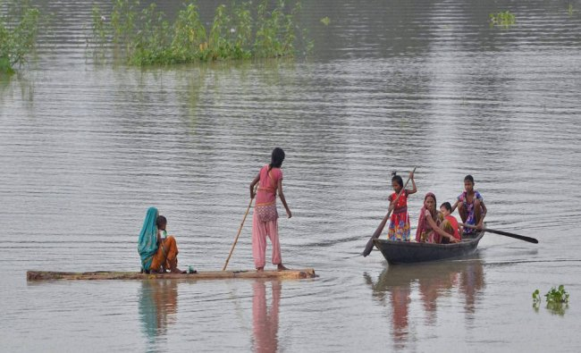 Women on a boat wade through flooded area after heavy showers in Mayong village in Morigoan...