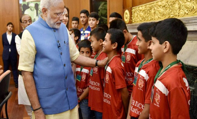 Prime Minister Narendra Modi interacting with the children at the launch of the Reliance...