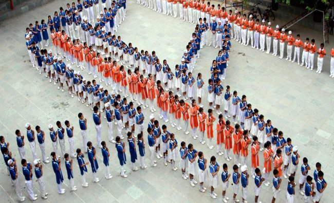 School students sit in the formation of a plane as they pray for the Indian Air Force plane...