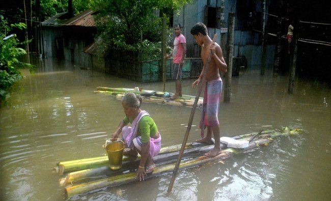 People use a banana raft to commute in a flooded area after heavy rains in Alipurduar...