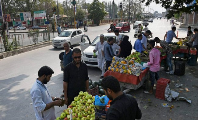 Vendors sell fruit at M A Road after curfew was lifted after 17-day in Srinagar on Tuesday...