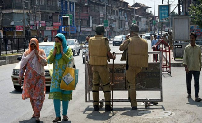 Policemen stands guard at Budshah Chowk after the 17-day old curfew was lifted in Srinagar on ...