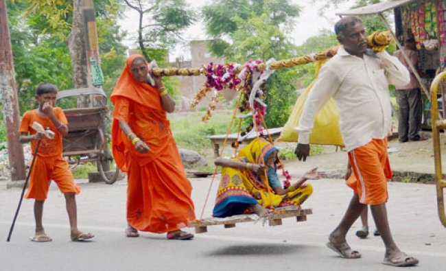 A couple carry their mother Runuka Devi on a palanquin to Gola Gokarannath from Kachla Ganga Ghaat..