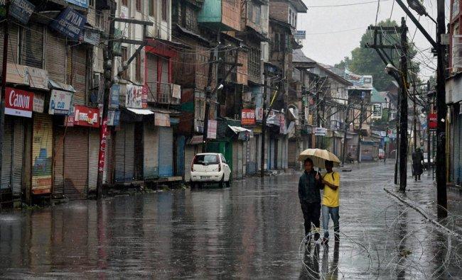 Boys walk with an umbrella during rains in Srinagar on Wednesday...