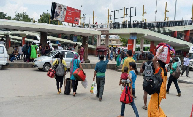 Commuters walk with their belongings as buses were off the roads as the KSRTC employees\' strike...