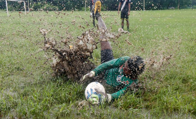 A man dives to catch the ball during fotball practice in a public park in Kolkata...