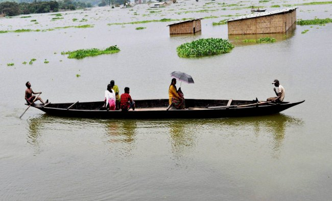 Villagers move to safe place in a boat from the flooded Panikhiti area in Kamrup district of Assam..