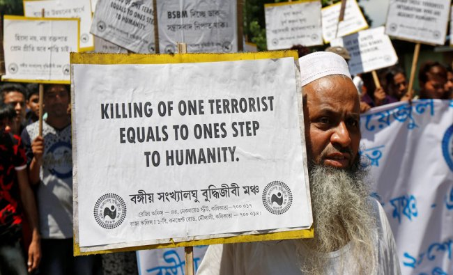 A demonstrator holds a placard during a protest organised by a Muslim minority forum...
