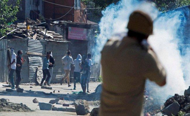 A policeman fires teargas shell to disperse protesters during a clash in Srinagar...