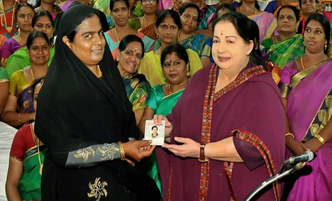 Jayalalithaa presents a primary membership card to a newly joined party worker...