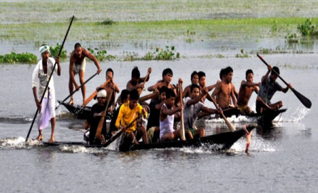 Villagers take part in traditional Boat race in flood water in Morigaon district of Assam...