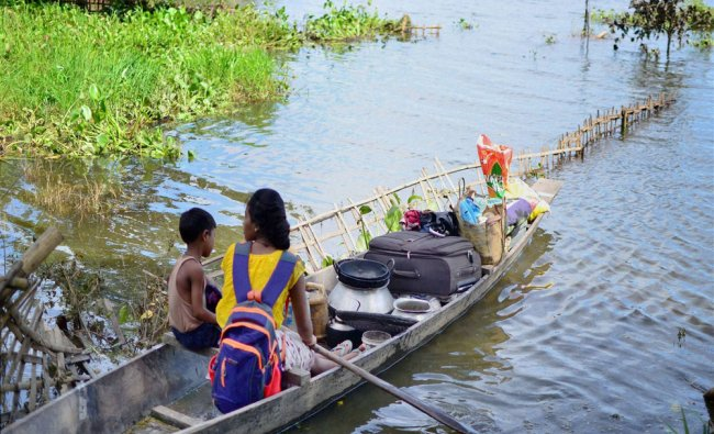 Two children rowing a country boat to cross flood water at the flood affected Kaziranga...