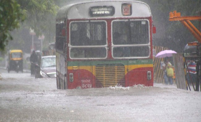 Vehicles plying at a flooded road during heavy rains in Mumbai...