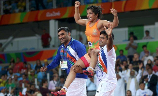 Sakshi Malik (IND) of India celebrates with her team members after winning...