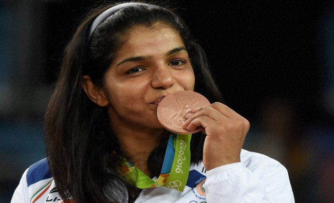 India\'s Sakshi Malik poses with her bronze medal for....