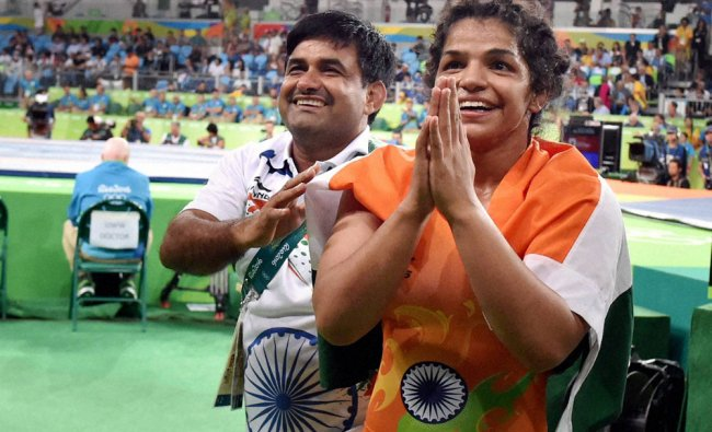 India\'s Sakshi Malik along with her coach Kuldeep Singh celebrates after winning bronze medal...
