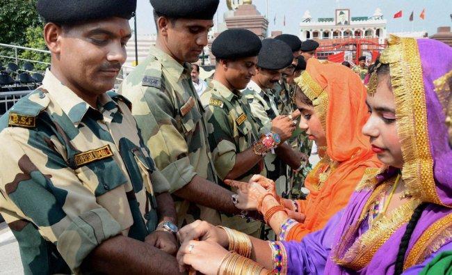School girls wearing traditional Punjabi dresses tying Rakhi to BSF jawans on the occasion...