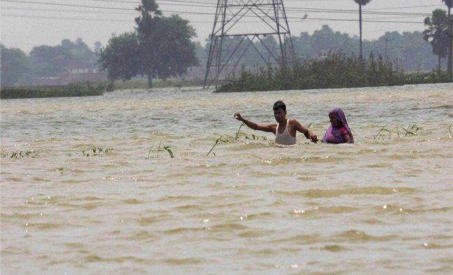 Villagers walk through flood waters at a village in Patna district of Bihar...