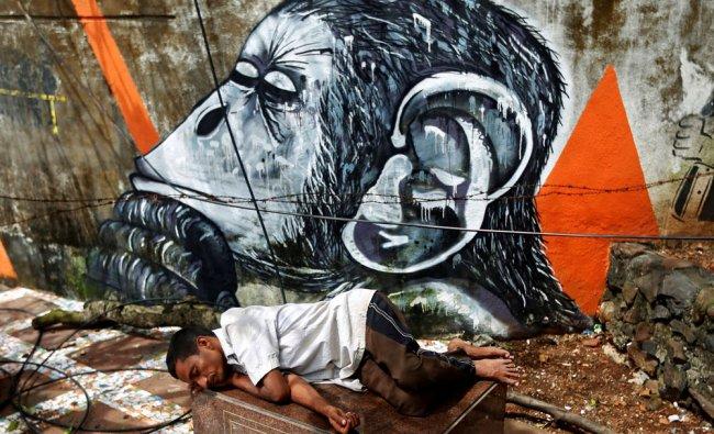 A man sleeps on a stone plaque inside a park in Mumbai, India...