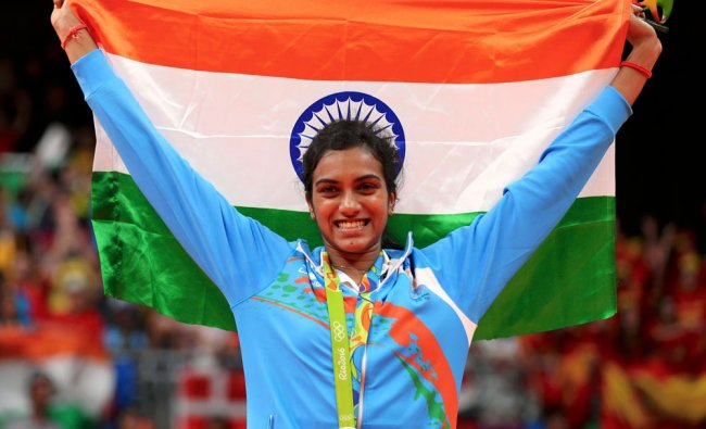 Silver medallist P.V. Sindhu (IND) of India poses with an Indian national flag...