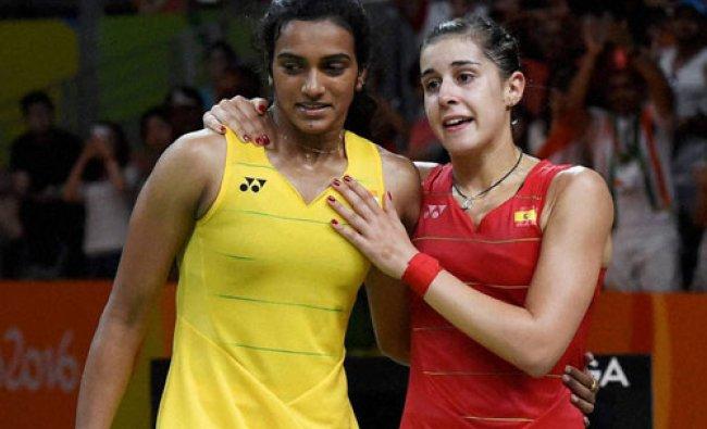 Silver medalist V. Sindhu Pusarla of India, greets gold medalist Carolina Marin of Spain