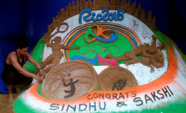Sand artist makes a sand art to greet two Indian Olympics medal winners Sindhu and Sakhi...