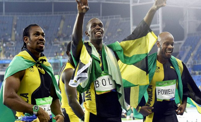 Jamaica\'s Usain Bolt (C) with team members celebrates winning the gold in men\'s 4x100-meter...